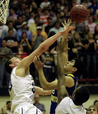 Boerne Champion's Dallas Quick (left) blocks a shot by Alamo Heights' Brandon Garcia (right) in Class 4A basketball playoffs at Littleton Gym on Wednesday, Mar. 2, 1011. Kin Man Hui/kmhui@express-news.net Photo: KIN MAN HUI, Kin Man Hui/kmhui@express-news.net / San Antonio Express-News