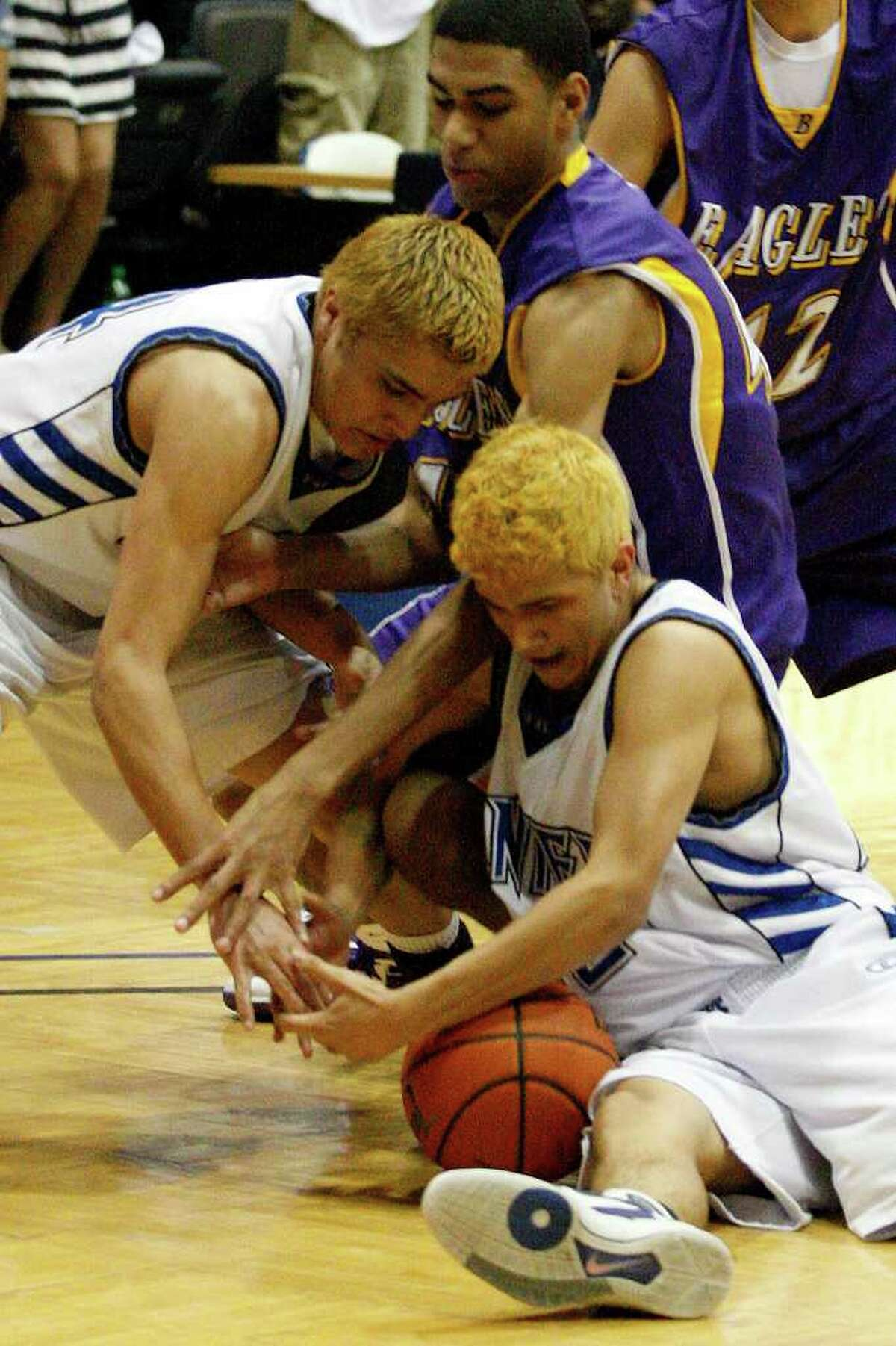 BKB -- Lanier Voks Martin Sanchez, left, and Joe Louis Gonzales, right, box out Brackenridge Eagles Gabriel Taylor late in overtime of the Region IV Quarterfinals at Greehey Arena of St. Mary's University, Wednesday, March 2, 2011. Lanier went on to win 51-47. JERRY LARA/glara@express-news.net