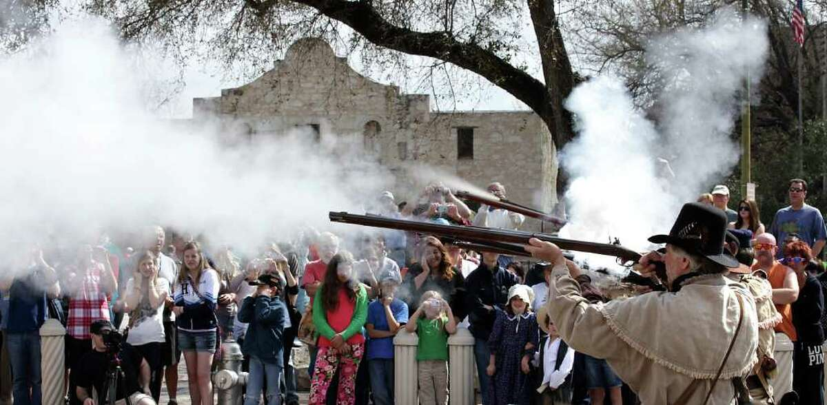 Alamo re-enactors fire their rifles for a crowd in front of the Alamo. Native Sun Productions is presenting