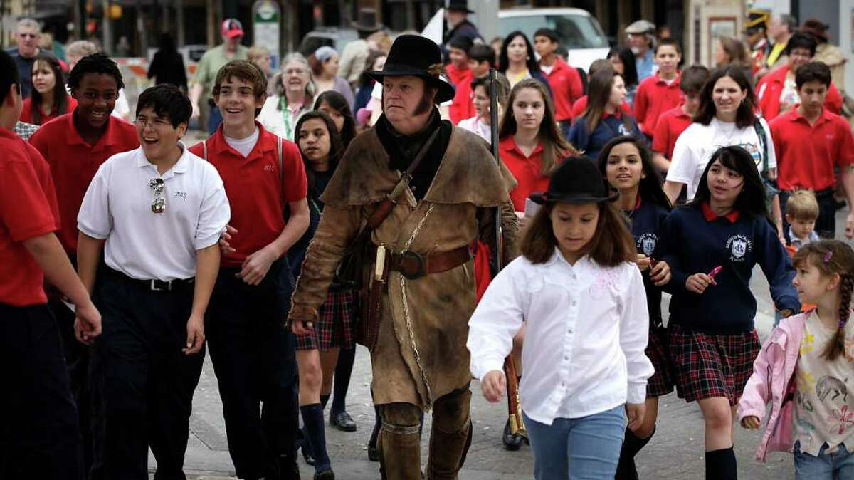 William Sheets, center, an Alamo period re-enactor, gives a walking tour with students during