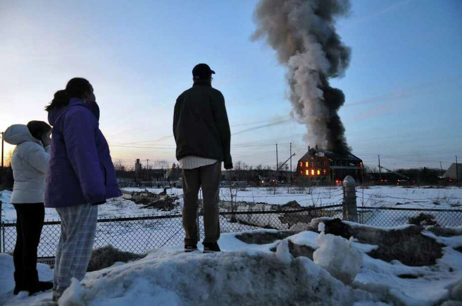 Spectators stand on a snow bank to watch firefighters douse flames on a building at R Kelly Freedman & Son Inc. scrap yard  on Thursday  evening March 3, 2011, in Green Island.  The plume of smoke could be seen from miles away.( Philip Kamrass / Times Union ) Photo: Philip Kamrass