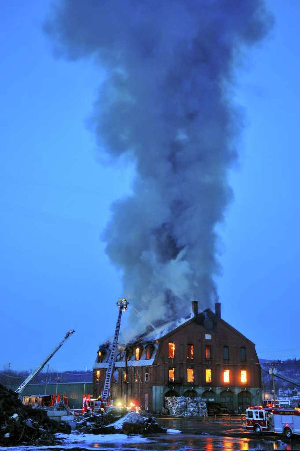 Firefighters douse flames on a building at R. Kelly Freedman & Son Inc. scrap yard on Thursday evening March 3, 2011, in Green Island, NY. The plume of smoke could be seen from miles away .( Philip Kamrass / Times Union )