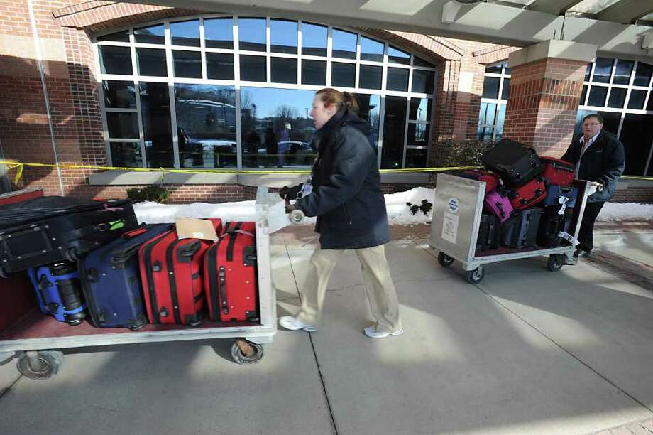 Luggage is wheeled to the baggage claim area after an incident at the Albany International Airport in Colonie, NY on Thursday, March 3, 2011. A cracked battery, in the back up supplies for the airport phone system, caused fumes and was cause for an evacuation on the baggage claim area. (Lori Van Buren / Times Union) Photo: Lori Van Buren
