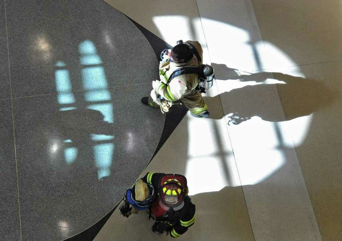 Firemen check out an evacuated baggage claim area of the Albany International Airport in Colonie, NY on Thursday, March 3, 2011. A cracked battery, in the back up supplies for the airport phone system, caused fumes and was cause for an evacuation on the baggage claim area. (Lori Van Buren / Times Union)