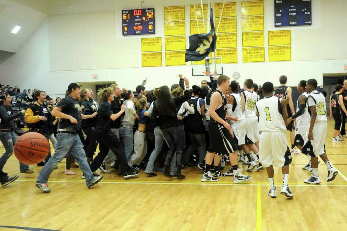 Notre Dame basketball player and fans celebrate the team's win after Thursday's SWC boys basketball final at Weston High School on March 3, 2011.