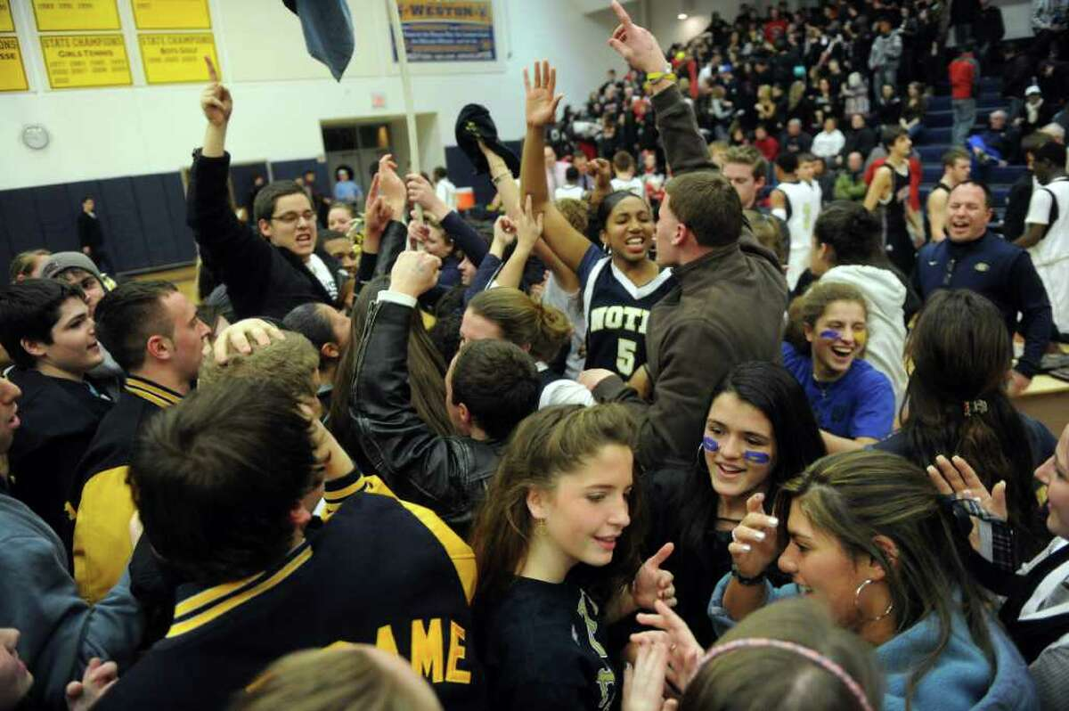 Notre Dame fans gather on the court to celebrate their team's win after Thursday's SWC boys basketball final at Weston High School on March 3, 2011.