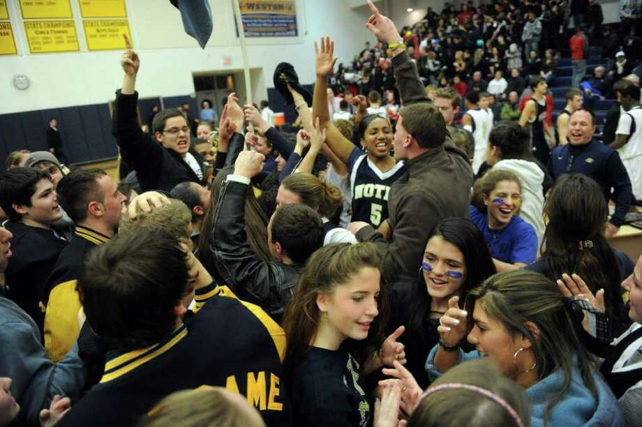 Notre Dame fans gather on the court to celebrate their team's win after Thursday's SWC boys basketball final at Weston High School on March 3, 2011. Photo: Lindsay Niegelberg / Connecticut Post