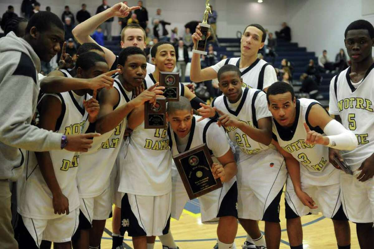 Notre Dame players gather with their awards after winning Thursday's SWC boys basketball final at Weston High School on March 3, 2011.