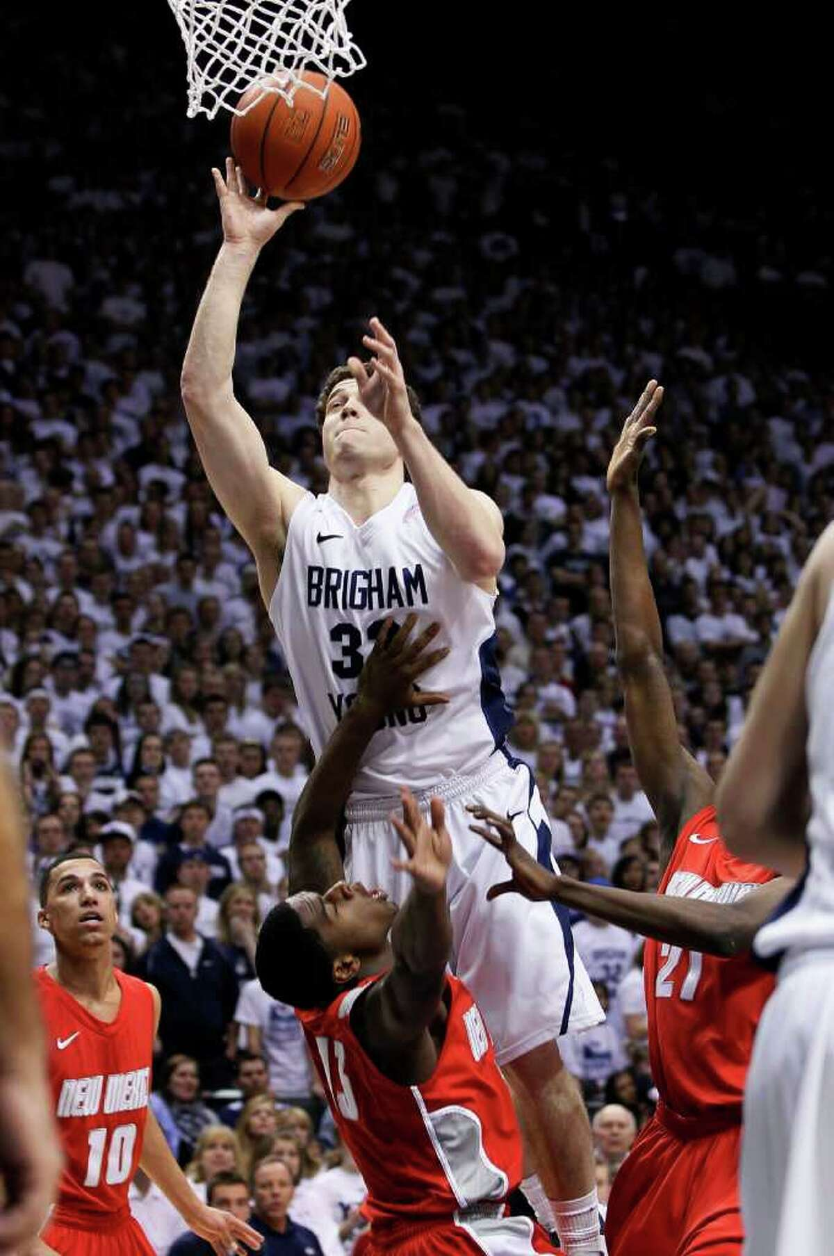 BYU guard Jimmer Fredette (32) attempts to score over New Mexico guard Jamal Fenton (13) during the first half of an NCAA college basketball game in Provo, Utah, Wednesday, March 2, 2011. Fredette was called for charging on the play. (AP Photo/Colin E Braley)