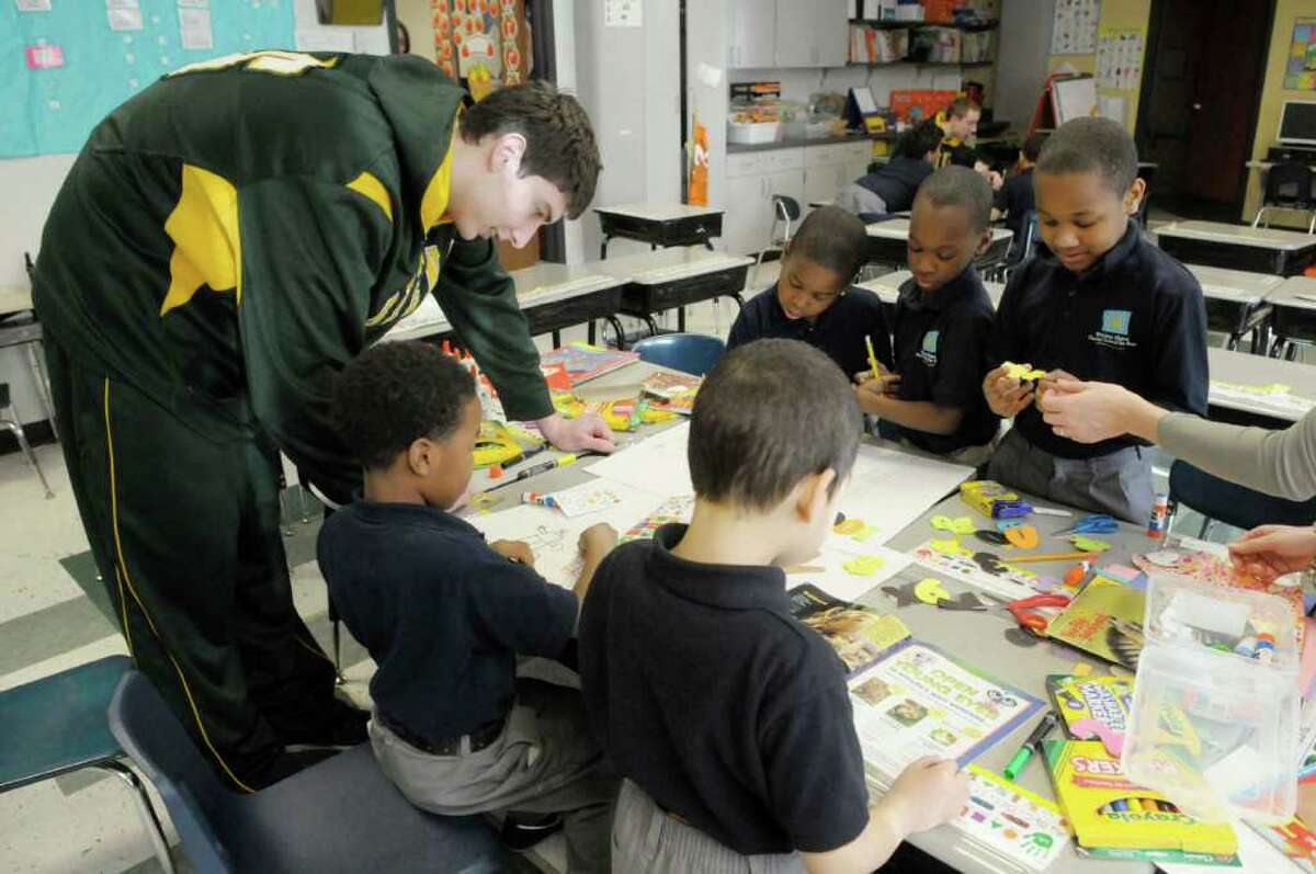Siena basketball player, Ryan Rossiter, left, works with first graders on an art project at Brighter Choice Charter School in Albany, NY on Wednesday, Jan. 5, 2011. Three players and one assistant coach from Siena came to the school to answer questions posed by students and to work with first graders in different activities. (Paul Buckowski / Times Union)