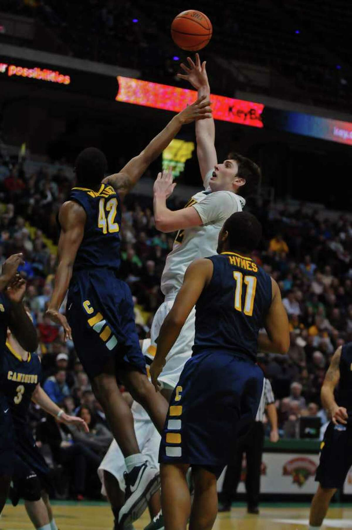 Siena's Ryan Rossiter puts up a shot over Canisius Tomas Vasquez-Simmons during the second half of Siena's 73-69 win over Canisius at the Times Union Center in Albany, NY on Monday night January 17, 2011. ( Philip Kamrass / Times Union )