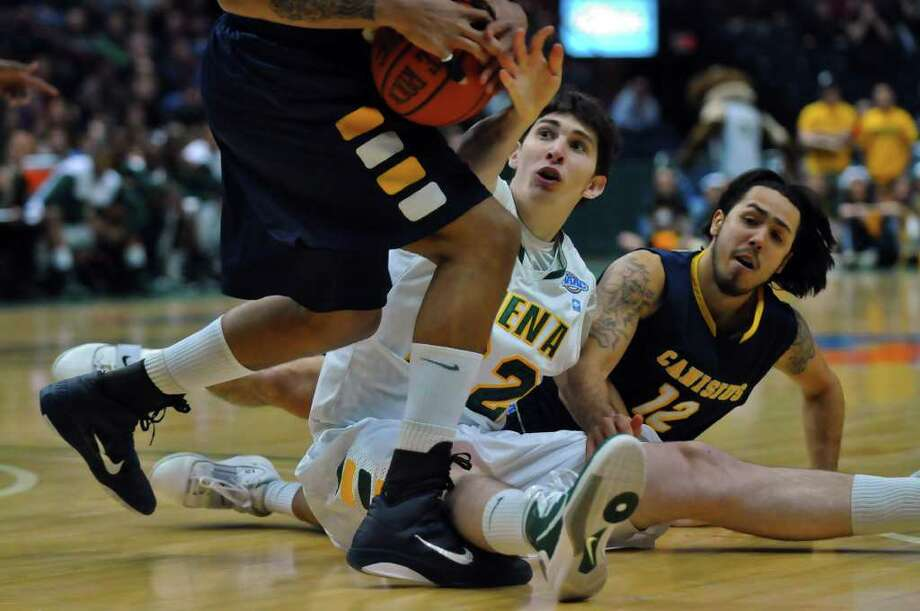 Siena's Ryan Rossiter, center,  and Canisius Gaby Belardo, right,  battle for a loose ball during the first half of Siena's 73-69 win over Canisius at the Times Union Center in Albany, NY on Monday night January 17, 2011. ( Philip Kamrass / Times Union ) Photo: Philip Kamrass / 00011629A