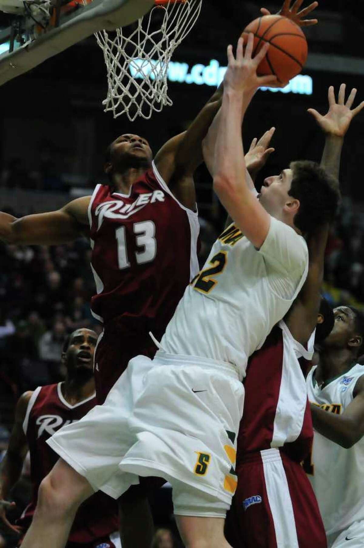 Siena's Ryan Rossiter is defended by Rider's Danny Stewart, left, and Novar Gadson, mostly obscured at right, during the second half of Siena's 68-60 loss at the Times Union Center in Albany, NY, on Monday January 24, 2011. ( Philip Kamrass / Times Union )