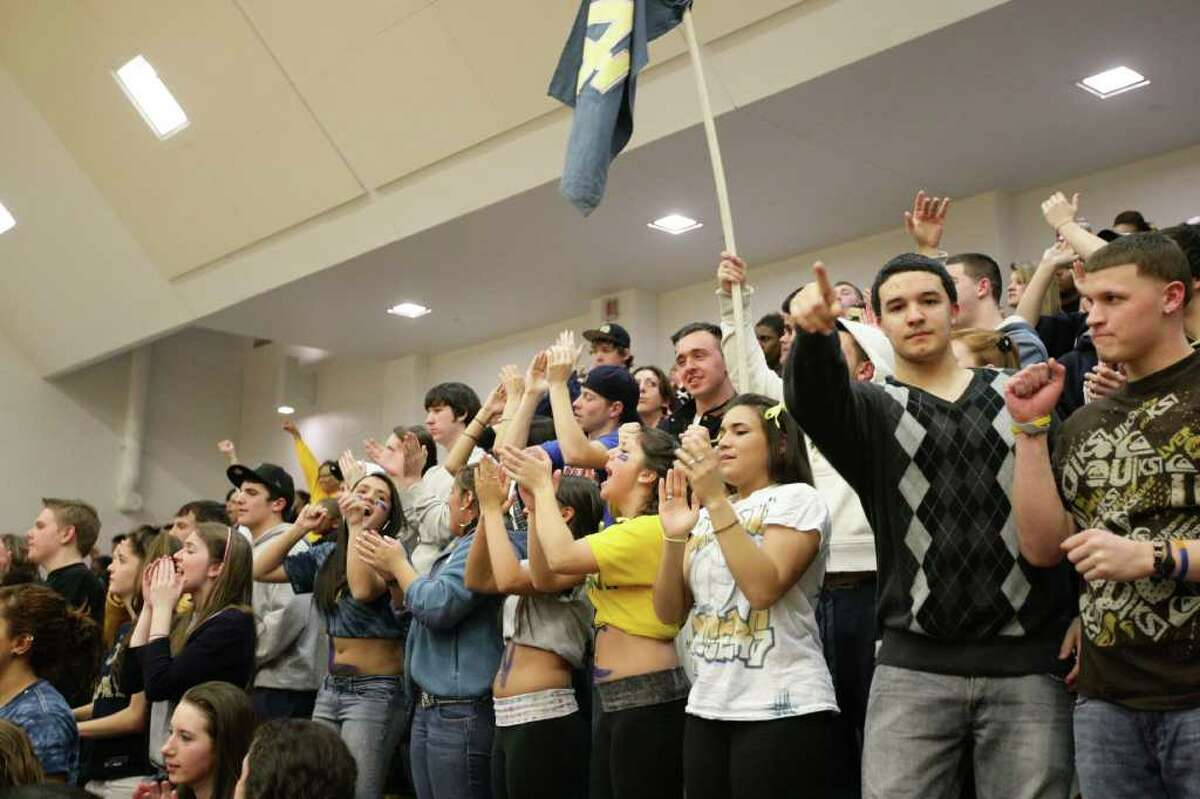 Students and fans cheer Pomperaug High School and Notre Dame Catholic High School during the SWC high school men's basketball championship at Weston High School in Weston, Conn. on March 3, 2011.