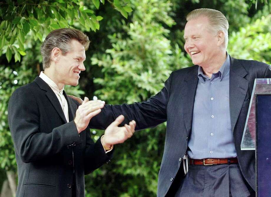 "Actor Jon Voight, right, congratulates singer-actor Randy Travis as he introduces him during dedication ceremonies for Travis' star on the Hollywood Walk of Fame in Los Angeles' Hollywood district Wednesday, Sept. 29, 2004.  Travis has been a prominent voice in country music for nearly 20 years and has won numerous Grammy and other awards, and has appeared in several feature and television movies and series.  Voight and Travis both starred in the feature, ""The Rainmaker."" Photo: REED SAXON, AP / AP"