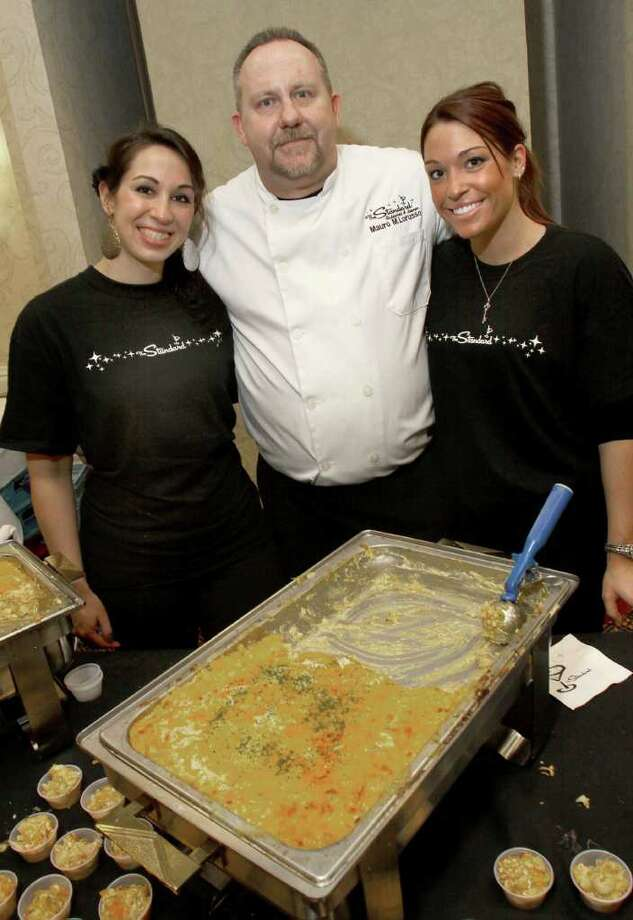 The Standard's executive chef, Mauro M. Lorusso, center, and servers Laurena Villa, left, and Danielle Losowski pose behind their mac-n-cheese, which won the people's choice second place award at the Table Hopping/timesunion.com Mac-N-Cheese Bowl to benefit the Regional Food Bank.  (Photo by Joe Putrock / Special to the Times Union) Photo: Joe Putrock / JP