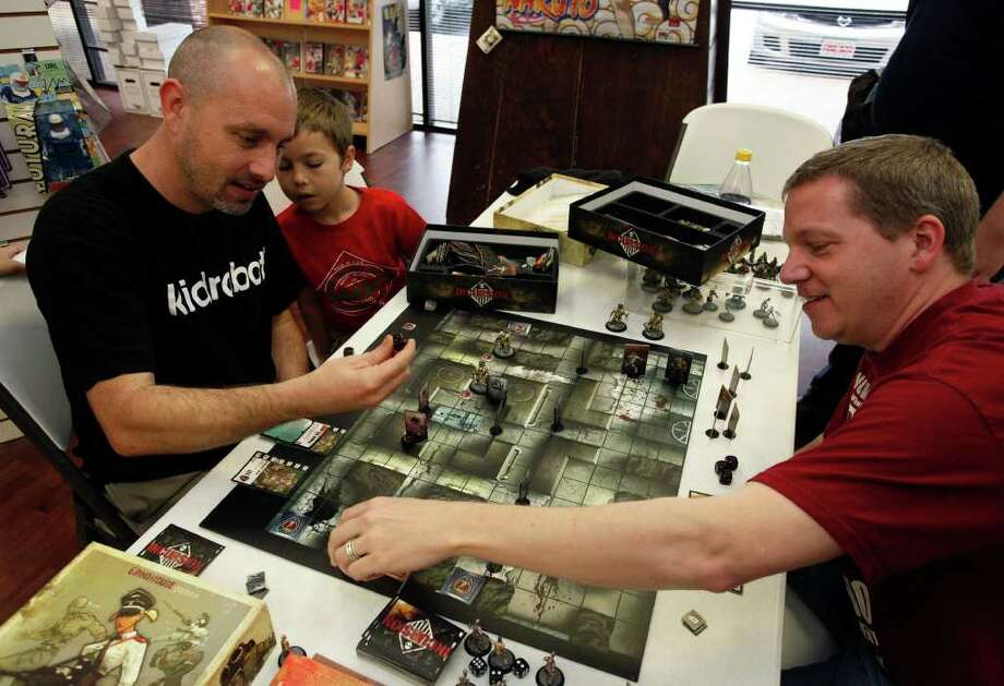 SA LIFE; INCURSION JMS; 02/18/2011; With Jim's son Luke, age 7, looking on, brothers Jim, left, and John Bailey play the board game Incursion, which they invented, February 19, 2011 at Dragon's Lair in San Antonio. ( Photo by J. Michael Short ) Photo: J. Michael Short, FREELANCER / San Antonio Express-News