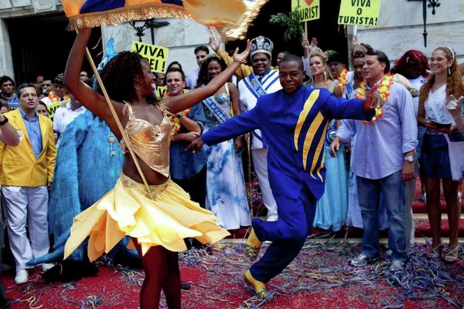 Members of the Unidos da Tijuca samba school dance during a ceremony marking the official opening Carnival season in Rio de Janeiro, Brazil, Friday, March 4, 2011. (AP Photo/Rodrigo Abd) Photo: Rodrigo Abd