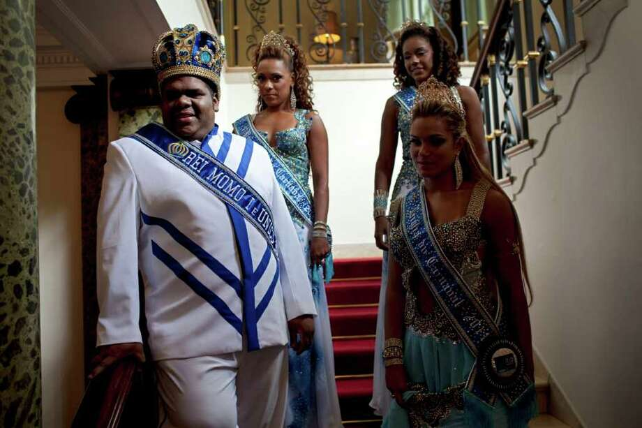 This year's King Momo, the crowned and costumed Milton Rodrigues, front left, flanked by the Carnival queen and two princesses, waits before a ceremony marking the official opening Carnival season in Rio de Janeiro, Brazil, Friday, March 4, 2011. Covered in confetti and to the sound of drums, Rio's mayor Eduardo Paes handed the key to the city to King Momo, the mythical figure who reigns over the chaos of Carnival, officially opening this seaside city's five-day annual exaltation of music, booze and flesh. (AP Photo/Rodrigo Abd) Photo: Rodrigo Abd