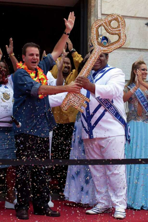 Rio's mayor Eduardo Paes, left, hands the key of the city to this year's King Momo, the crowned and costumed Milton Rodrigues, right, during a ceremony marking the official opening Carnival season in Rio de Janeiro, Brazil, Friday, March 4, 2011. (AP Photo/Rodrigo Abd) Photo: Rodrigo Abd