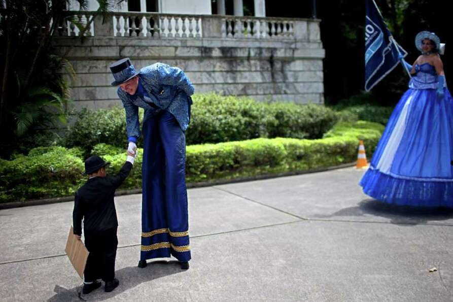 A reveler on stilts greets a boy during a ceremony marking the official opening Carnival season in R