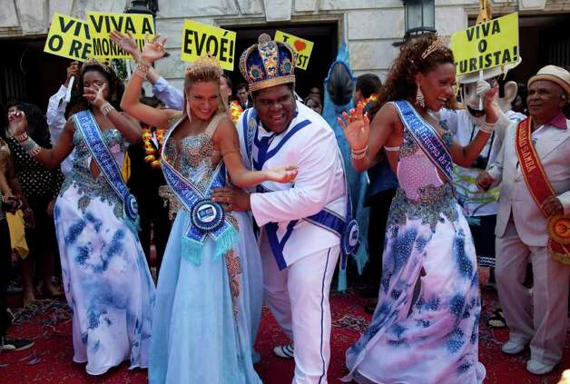 This year's King Momo, the crowned and costumed Milton Rodrigues, center, flanked by the Carnival queen and two princesses, pose for pictures during carnival celebrations in Rio de Janeiro, Brazil, Friday, March 4, 2011. Covered in confetti and to the sound of drums, Rio's mayor Eduardo Paes handed the key to the city to King Momo, the mythical figure who reigns over the chaos of Carnival, officially opening this seaside city's five-day annual exaltation of music, booze and flesh. (AP Photo/Rodrigo Abd) Photo: Rodrigo Abd
