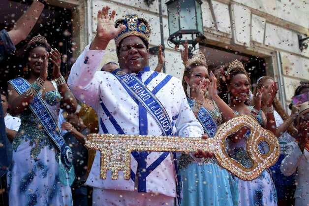 This year's King Momo, the crowned and costumed Milton Rodrigues, second from left, flanked by the Carnival queen and two princesses, waves as he holds up the key of the city during carnival celebrations in Rio de Janeiro, Brazil, Friday, March 4, 2011. Covered in confetti and to the sound of drums, Rio's mayor Eduardo Paes handed the key to the city to King Momo, the mythical figure who reigns over the chaos of Carnival, officially opening this seaside city's five-day annual exaltation of music, booze and flesh. (AP Photo/Rodrigo Abd) Photo: Rodrigo Abd