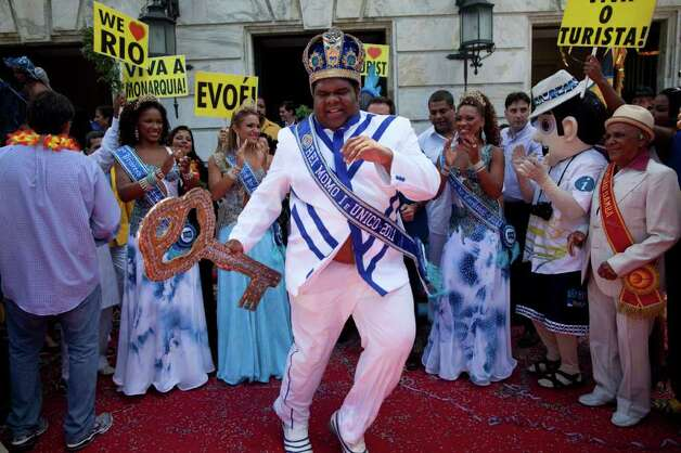 This year's King Momo, the crowned and costumed Milton Rodrigues, center, dances as he holds the key of the city during carnival celebrations in Rio de Janeiro, Brazil, Friday, March 4, 2011. Covered in confetti and to the sound of drums, Rio's mayor Eduardo Paes handed the key to the city to King Momo, the mythical figure who reigns over the chaos of Carnival, officially opening this seaside city's five-day annual exaltation of music, booze and flesh. (AP Photo/Rodrigo Abd) Photo: Rodrigo Abd