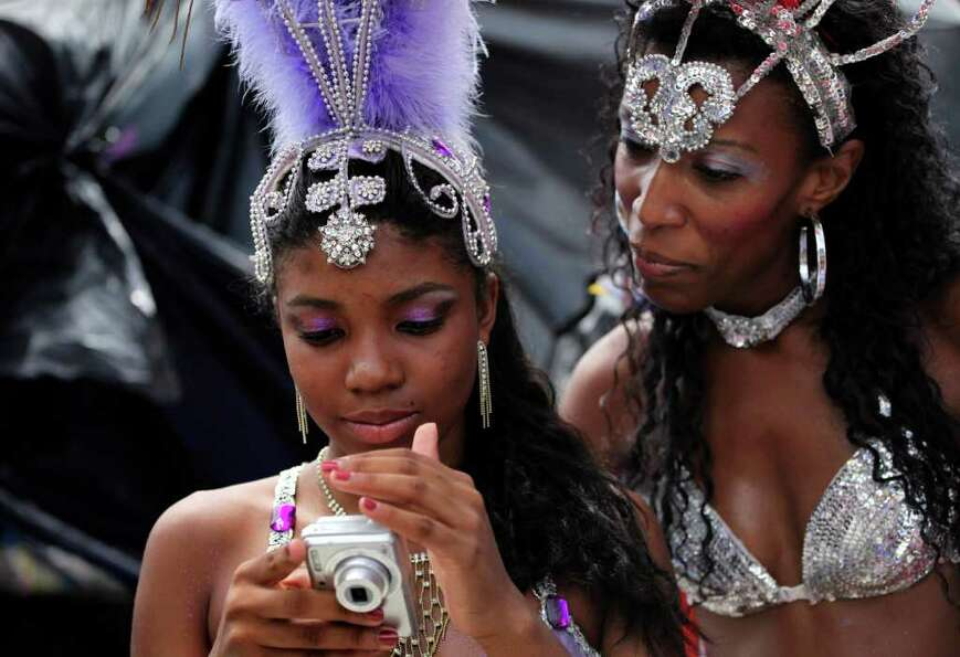 Women check pictures in a camera at the Sambadrome in Rio de Janeiro, Brazil, Friday, March 4, 2011.