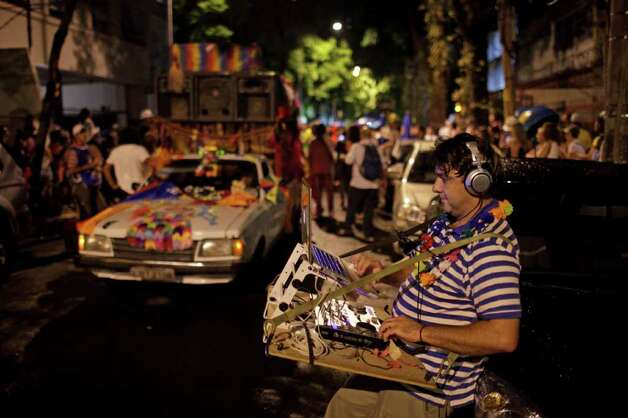 A DJ controls the sound wirelessly during the 'Mameludicos Euforicos' street carnival parade in Rio de Janeiro, Brazil, Thursday, March 3, 2011. (AP Photo/Felipe Dana) Photo: Felipe Dana