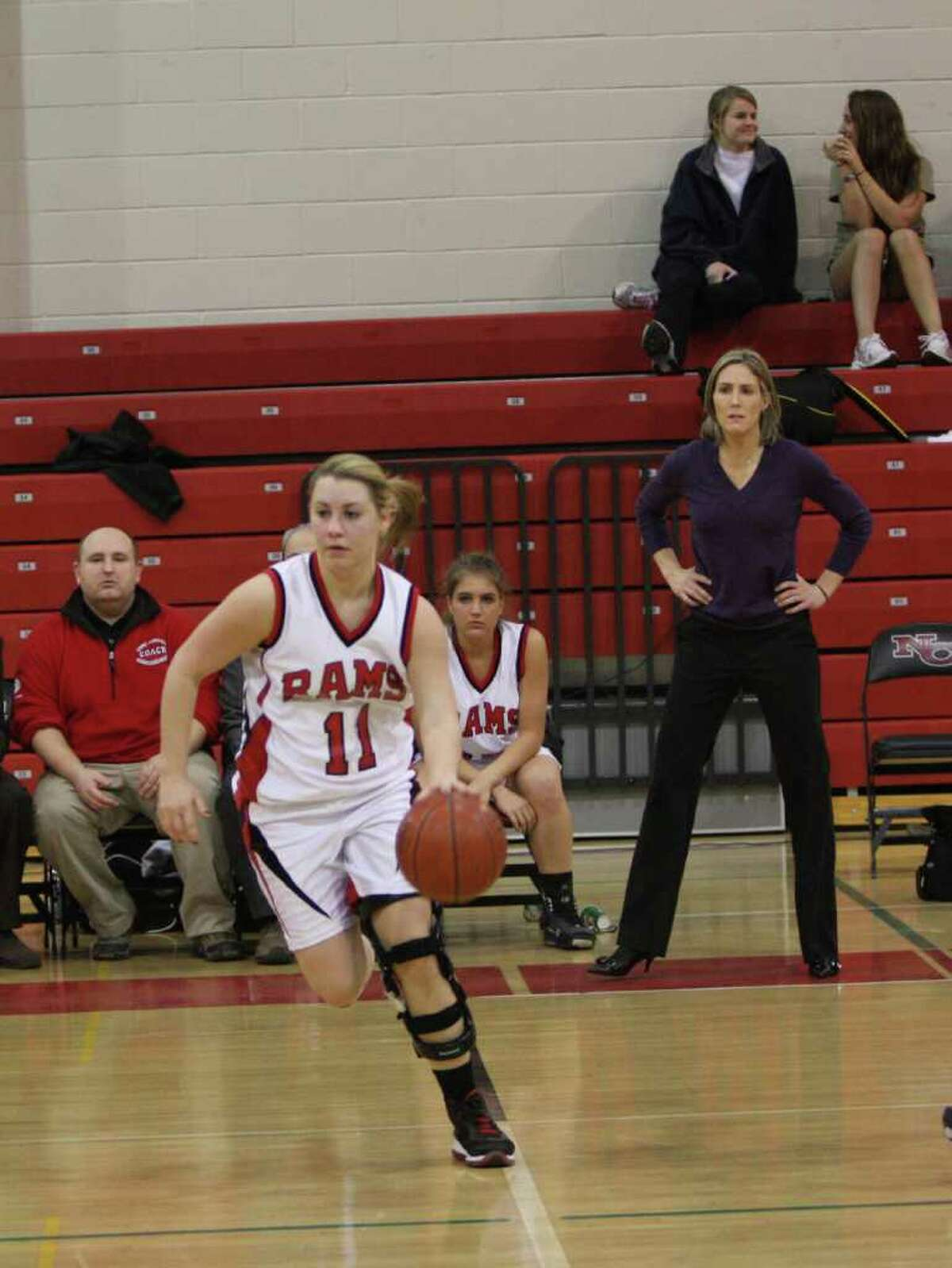 New Canaan's Courtney Rodges brings the ball up court as coach Kim Palmer looks on during the Rams' 48-36 loss to RHAM in the Class L playoffs on Wednesday, March 3.