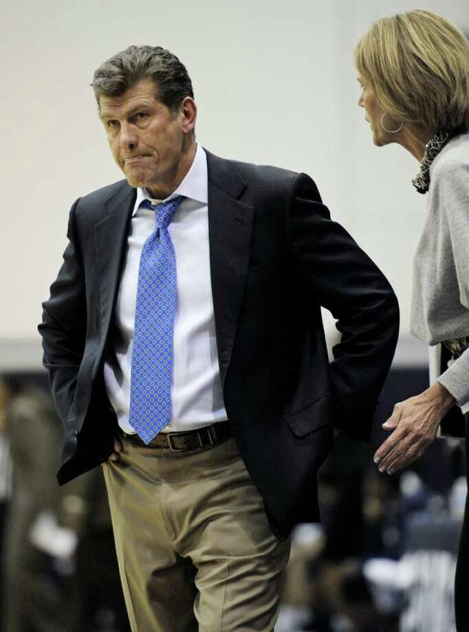 Connecticut women's baskball associate head coach Chris Dailey, right, talks to head coach Geno Auriemma as Georgetown pulls within 4 points during the second period of their Big East game in Washington, Saturday, Feb. 26, 2011. Connecticut defeated Georgetown 52-42. (AP Photo/Cliff Owen) Photo: AP