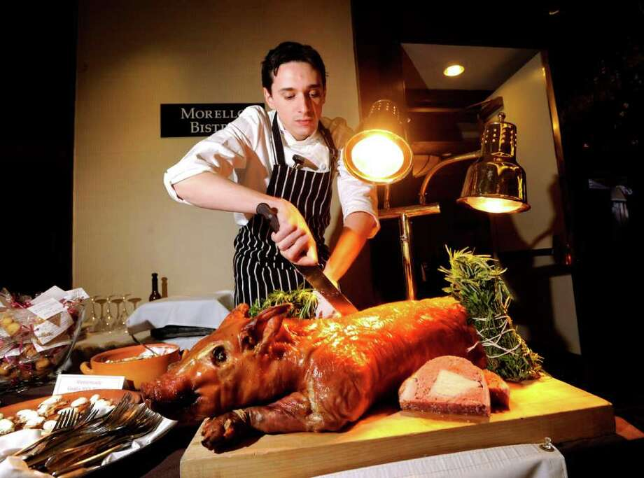 Executive Chef Mark Medina-Rios of Morello Italian Bistro of Greenwich carves the porchetta during the 26th annual Great Chefs at Hyatt Regency Greenwich, Friday night, March 4, 2011. Photo: Bob Luckey / Greenwich Time