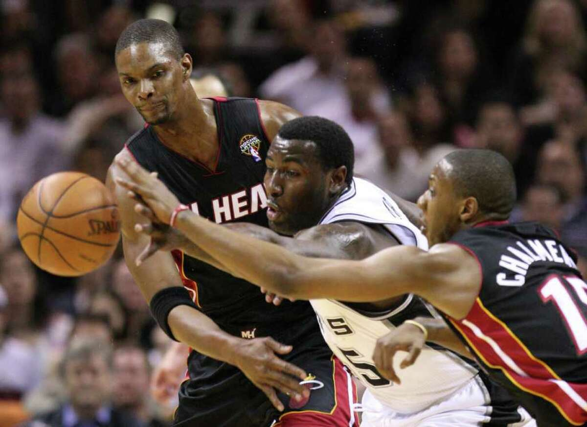 FOR SPORTS - San Antonio Spurs forward DeJuan Blair, center, fights for a loose ball with Miami Heat forward Chris Bosh (1) and Miami Heat guard Mario Chalmers (15) during first half action Friday March 4, 2011 at the AT&T Center. (PHOTO BY EDWARD A. ORNELAS/eaornelas@express-news.net)