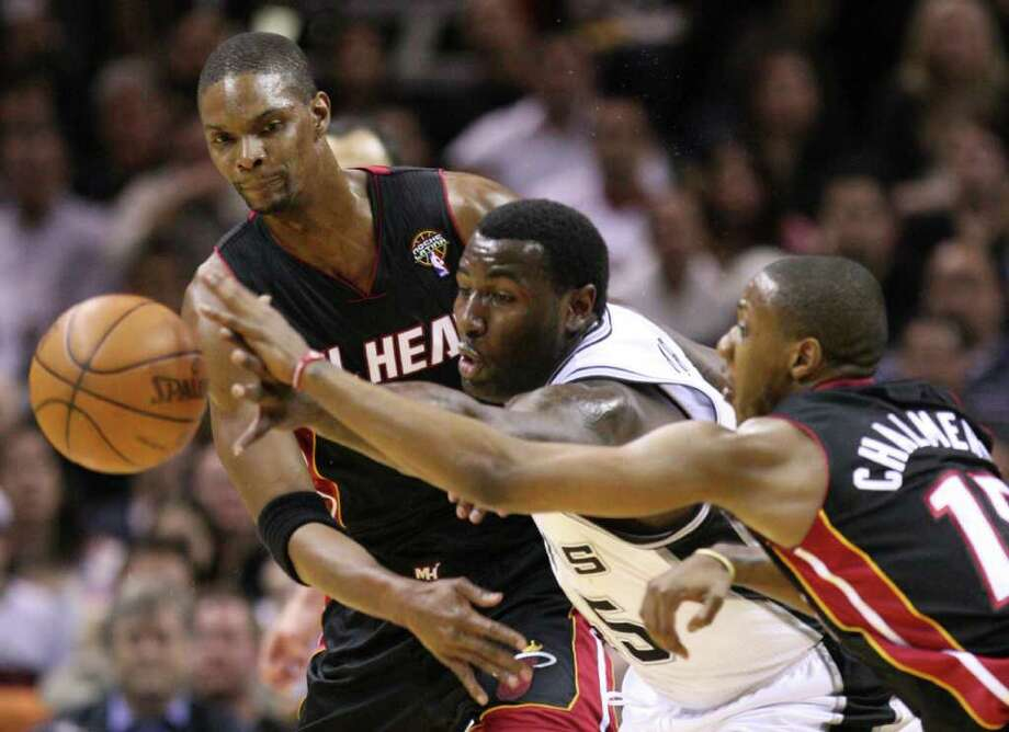 FOR SPORTS -  San Antonio Spurs forward DeJuan Blair, center, fights for a loose ball with Miami Heat forward Chris Bosh (1) and Miami Heat guard Mario Chalmers (15) during first half action Friday March 4, 2011 at the AT&T Center. (PHOTO BY EDWARD A. ORNELAS/eaornelas@express-news.net) Photo: EDWARD A. ORNELAS, SAN ANTONIO EXPRESS-NEWS / San Antonio Express-News NFS