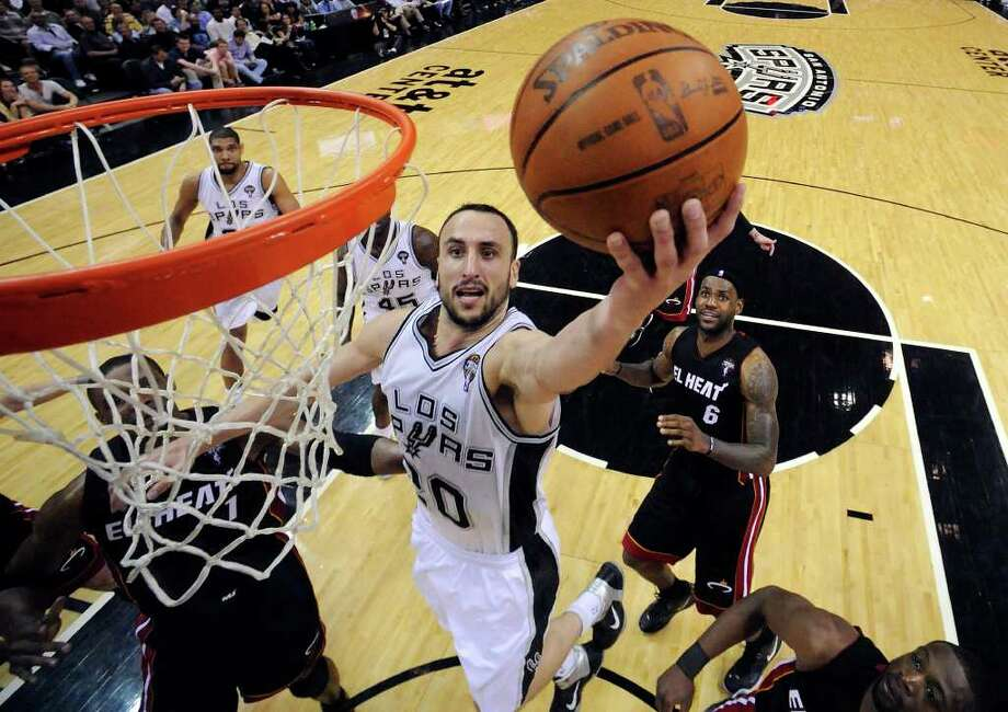 FOR SPORTS - Spurs' Manu Ginobili shoots between Heat defenders during second half action Friday March 4, 2011 at the AT&T Center. The Spurs won 125-95.  (PHOTO BY EDWARD A. ORNELAS/eaornelas@express-news.net) Photo: EDWARD A. ORNELAS, SAN ANTONIO EXPRESS-NEWS / SAN ANTONIO EXPRESS-NEWS NFS