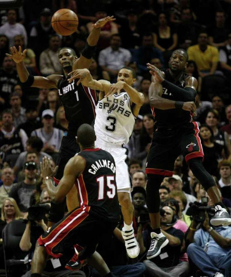 FOR SPORTS -  San Antonio Spurs guard George Hill (3) passes away from Miami Heat forward Chris Bosh (1), Miami Heat guard Dwyane Wade (3) and Miami Heat guard Mario Chalmers (15) during the second half of their NBA game at the AT&T Center in San Antonio, Texas Friday, March 4, 2011. (PHOTO BY KEVIN MARTIN/kmartin@express-news.net) Photo: KEVIN MARTIN, SAN ANTONIO EXPRESS-NEWS / San Antonio Express-News NFS
