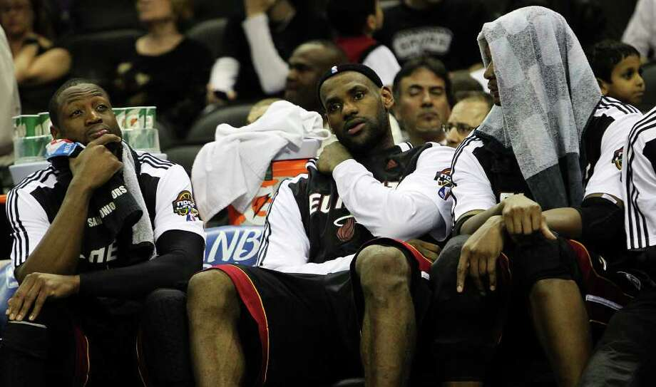 Miami Heat's Dwyane Wade (from left), LeBron James and Chris Bosh sit out the remaining few minutes of the game against the Spurs in the second half at the AT&T Center on Friday, Mar. 4, 2011. Spurs defeated the Heat, 125-95. Kin Man Hui/kmhui@express-news.net Photo: KIN MAN HUI, SAN ANTONIO EXPRESS-NEWS / San Antonio Express-News NFS