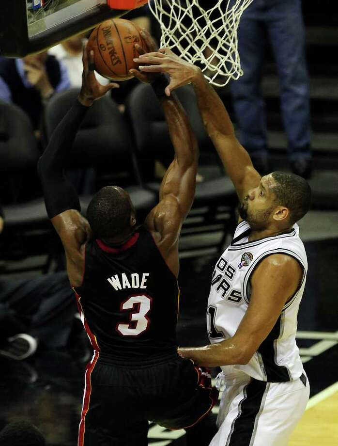 Spurs' Tim Duncan (right) attempts a block against Miami Heat's Dwyane Wade (03) in the first half at the AT&T Center on Friday, Mar. 4, 2011. Kin Man Hui/kmhui@express-news.net Photo: KIN MAN HUI, SAN ANTONIO EXPRESS-NEWS / San Antonio Express-News NFS