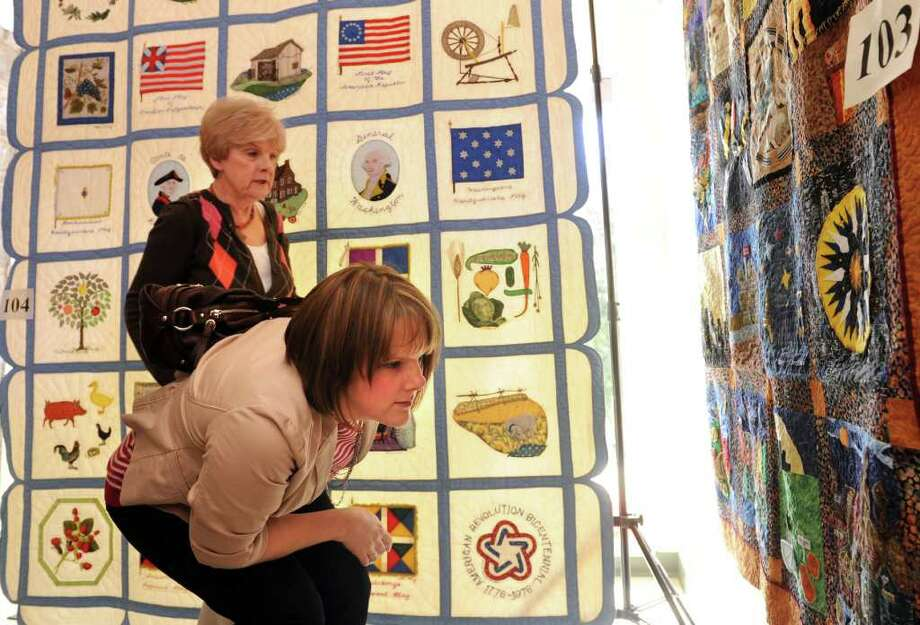 """Jen Mihalo, of Miller Place, NY, bends to look at a quilt constructed of blocks from a quilt challenge as Sue Hohn also admires the piece Friday, March 4, 2011 during the 9th annual Fabrics and Fabrications quilt exhibit at Southport Congregational Church in Southport, Conn.  Mihalo said her """"fingers hurt just looking at it."""" Photo: Autumn Driscoll / Connecticut Post"""