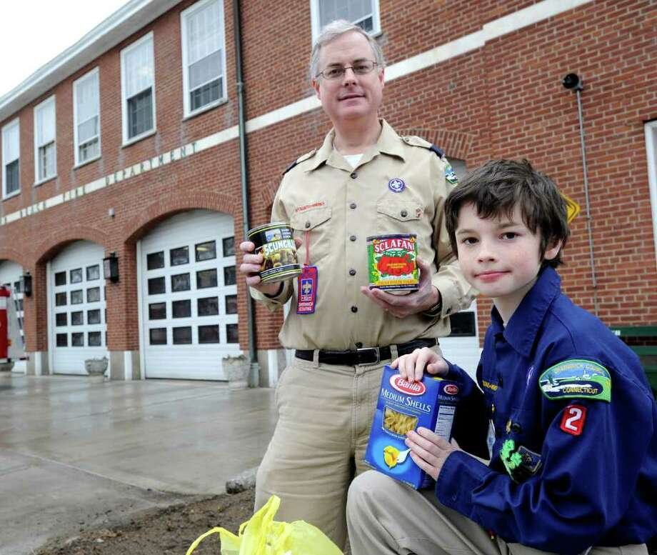 Boy Scout Evan Pey, 9, holds donated food with his father, Cubmaster Chris Pey, at the Sound Beach Fire Department, Old Greenwich, during a town-wide food drive by the Greenwich Boy Scouts and Cub Scouts to benefit Neighbor to Neighbor, Saturday morning, March 5, 2011. Photo: Bob Luckey / Greenwich Time