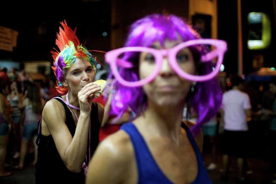 A reveler in costume eats a sandwich during a carnival parade in Rio de Janeiro, Brazil, Friday March 4, 2011. The five-day annual carnival celebration officially starts Friday and is expected to draw about 756,000 visitors, both foreign and Brazilian, who will pack hotels to nearly 100 percent capacity and spend about $559 million, according to Rio state's tourism department. (AP Photo/Rodrigo Abd) Photo: Rodrigo Abd, ASSOCIATED PRESS / Associated Press