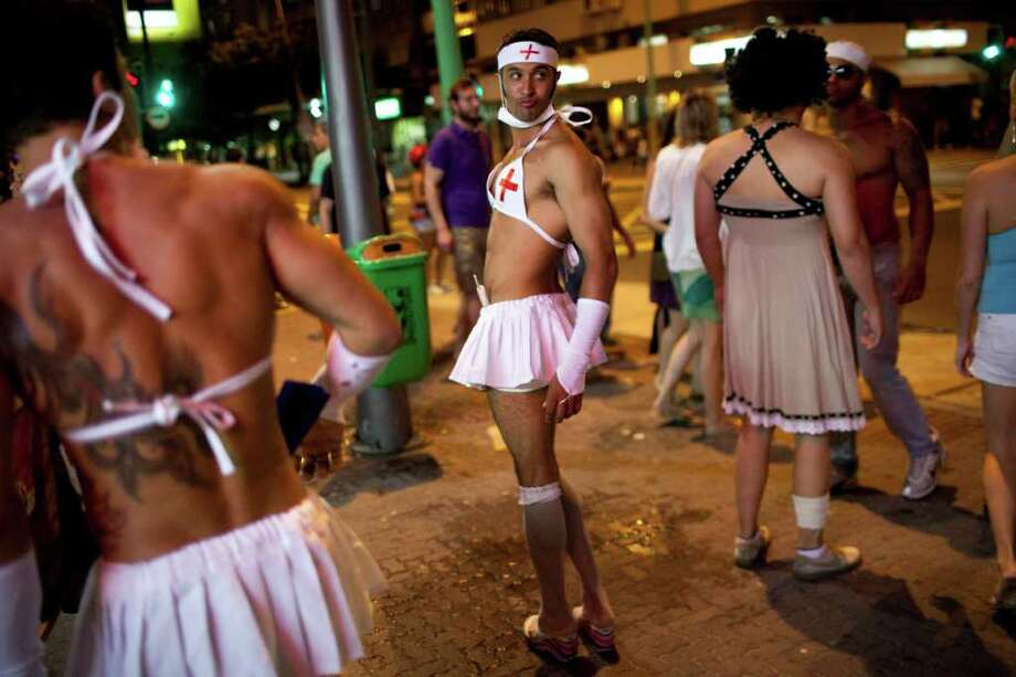 Revelers in costumes attend a carnival parade in Rio de Janeiro, Brazil, Friday March 4, 2011. The five-day annual carnival celebration officially starts Friday and is expected to draw about 756,000 visitors, both foreign and Brazilian, who will pack hotels to nearly 100 percent capacity and spend about $559 million, according to Rio state's tourism department. (AP Photo/Rodrigo Abd) Photo: Rodrigo Abd, ASSOCIATED PRESS / Associated Press