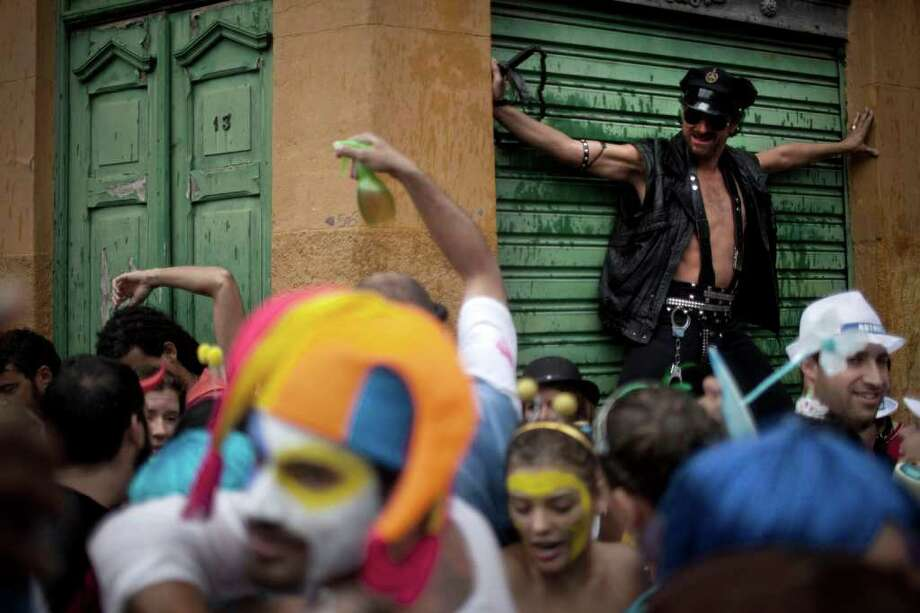"People dance during a ""Ceu na Terra"" street parade in Rio de Janeiro, Brazil, Saturday, March 5, 2011. The five-day annual carnival celebration officially started Friday and is expected to draw about 756,000 visitors, both foreign and Brazilian, who will pack hotels to nearly 100 percent capacity and spend about $559 million, according to Rio state's tourism department. (AP Photo/Felipe Dana) Photo: Felipe Dana, AP / Associated Press"