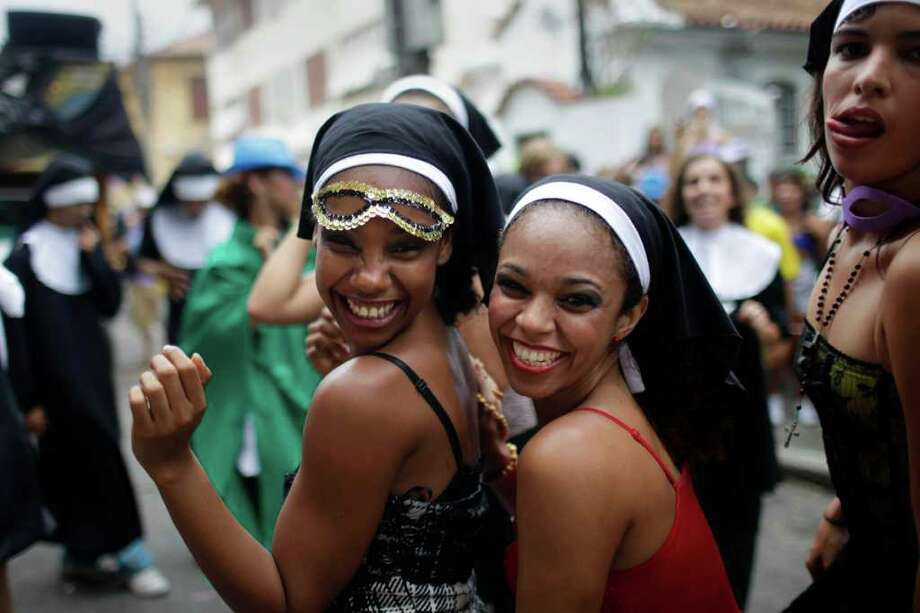 "Revelers dressed as nuns smiles during the ""Carmelitas"" street carnival parade in Rio de Janeiro, Brazil, Friday, March 4, 2011. ""Carmelitas"" is a band that started in 1991 by a group of friends who gathered for soccer and drinks just outside a convent of Carmelite nuns. Jokes about the possibility of nuns escaping to join the party gave rise to the band, which parades twice: once at the beginning of Carnival, when the nuns escape the convent to join the fun, and then on the last day, when they return to their cloistered existence. (AP Photo/Felipe Dana) Photo: Felipe Dana, ASSOCIATED PRESS / Associated Press"