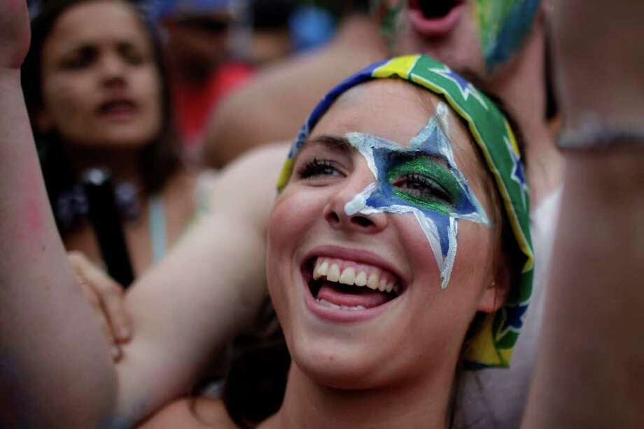 "A reveler laughs during the ""Carmelitas"" street carnival parade in Rio de Janeiro, Brazil, Friday, March 4, 2011. ""Carmelitas"" is a band started in 1991 by a group of friends who gathered for soccer and drinks just outside a convent of Carmelite nuns. Jokes about the possibility of nuns escaping to join the party gave rise to the band, which parades twice: once at the beginning of Carnival, when the nuns escape the convent to join the fun, and then on the last day, when they return to their cloistered existence. (AP Photo/Felipe Dana) Photo: Felipe Dana, ASSOCIATED PRESS / Associated Press"