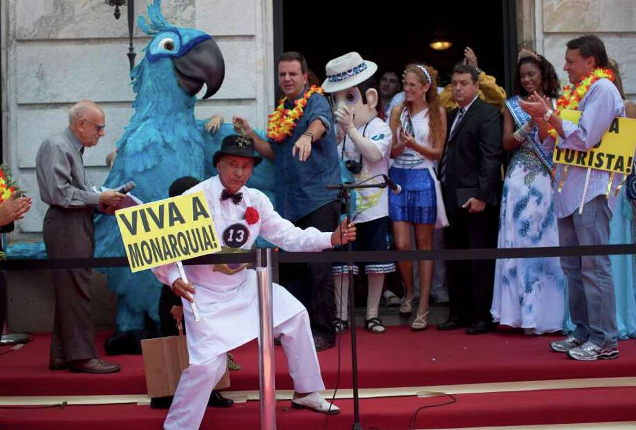 "A man, holding up a banner that reads in Portuguese ""Long live the monarchy,"" places a microphone before a ceremony marking the official opening Carnival season in Rio de Janeiro, Brazil, Friday, March 4, 2011. On top, third from left, Rio's mayor Eduardo Paes.  (AP Photo/Rodrigo Abd) Photo: Rodrigo Abd, ASSOCIATED PRESS / Associated Press"