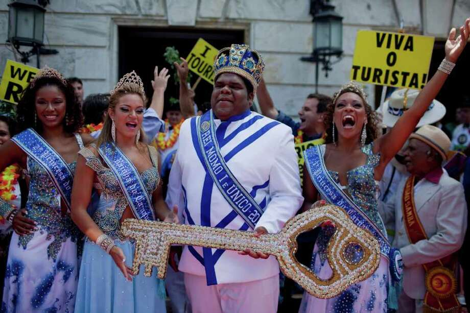 This year's King Momo, the crowned and costumed Milton Rodrigues, second from right, flanked by the Carnival queen and two princesses, holds up the key of the city during carnival celebrations in Rio de Janeiro, Brazil, Friday, March 4, 2011. Covered in confetti and to the sound of drums, Rio's mayor Eduardo Paes handed the key to the city to King Momo, the mythical figure who reigns over the chaos of Carnival, officially opening this seaside city's five-day annual exaltation of music, booze and flesh. (AP Photo/Rodrigo Abd) Photo: Rodrigo Abd, ASSOCIATED PRESS / Associated Press