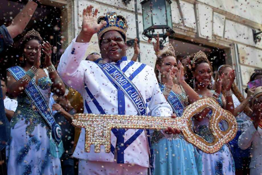 This year's King Momo, the crowned and costumed Milton Rodrigues, second from left, flanked by the Carnival queen and two princesses, waves as he holds up the key of the city during carnival celebrations in Rio de Janeiro, Brazil, Friday, March 4, 2011. Covered in confetti and to the sound of drums, Rio's mayor Eduardo Paes handed the key to the city to King Momo, the mythical figure who reigns over the chaos of Carnival, officially opening this seaside city's five-day annual exaltation of music, booze and flesh. (AP Photo/Rodrigo Abd) Photo: Rodrigo Abd, ASSOCIATED PRESS / Associated Press