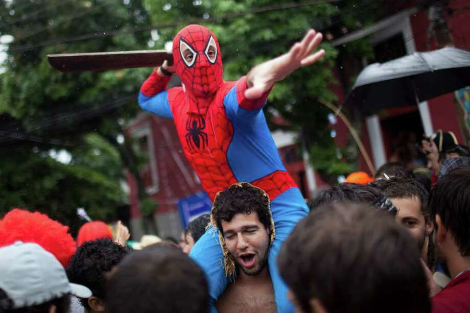 "A reveler, disguised as ""Spiderman,"" is carried on shoulders during a ""Ceu na Terra"" street parade in Rio de Janeiro, Brazil, Saturday, March 5, 2011. The five-day annual carnival celebration officially started Friday and is expected to draw about 756,000 visitors, both foreign and Brazilian, who will pack hotels to nearly 100 percent capacity and spend about $559 million, according to Rio state's tourism department. (AP Photo/Felipe Dana) Photo: Felipe Dana, AP / Associated Press"